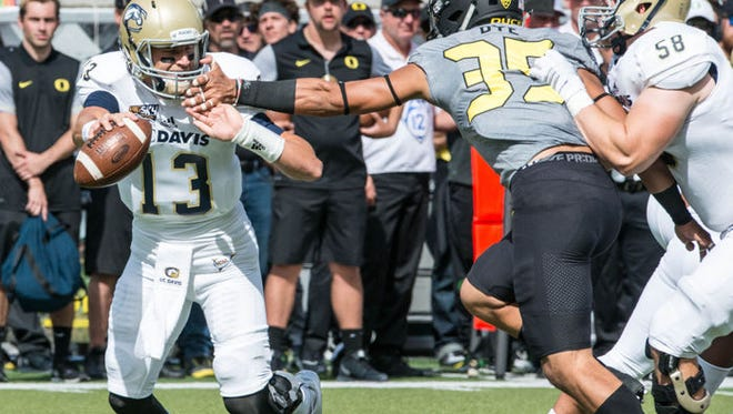 Oregon linebacker Troy Dye beats a block to sack UC Davis' Ben Scott in the second quarter. Dye was called for a facemask penalty on the play, giving the Aggies a first down.