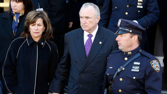 New York Police Department commissioner William Bratton, center, walks with his wife Rikki Klieman, left, following funeral services for officer Rafael Ramos at Christ Tabernacle Church in Queens, New York, on Saturday, Dec. 27, 2014.