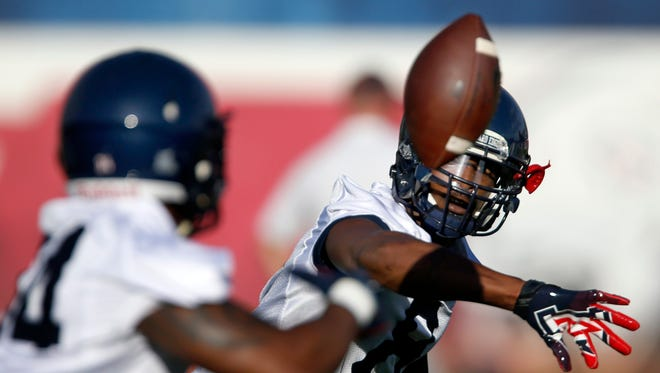 Quarterback Jerrard Randall pitches the ball to a running back on the opening day of practice for Arizona on Wednesday August 5, 2015,