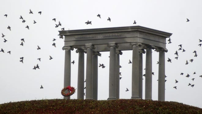 Starlings fly around the James Whitcomb Riley memorial and burial place on a quiet gray day.