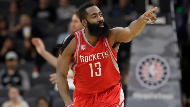 Houston Rockets guard James Harden signals to a teammate during the second half of the Rockets' NBA basketball game against the San Antonio Spurs.