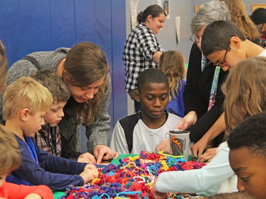 From left to right: Lucian Meister, 5, Julian Meister, 7, and their mother, Emily Meister, along with Corey Norfleet, 12, work on weaving at a craft station at the 2017 Martin Luther King Jr. Day of Service at Grant Wood Elementary in Iowa City on Jan. 16, 2017.