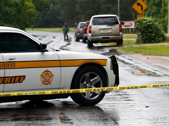 A Lincoln County Sheriff's vehicle and evidence tape block a street Sunday, May 28, 2017, in Brookhaven, Miss., where several people were fatally shot Saturday evening. A man was arrested Sunday in the house-to-house shooting rampage that left several people dead, including a sheriff's deputy.