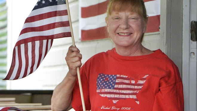 Erie resident Kathleen Bartoe, 60, takes a break from playing with three of her grandchildren on Saturday after they counted U.S. flags soon to be used to honor veterans.