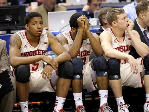 IndianaÕs Devin Davis,left, Jeremy Hollowell and Austin Etherington sit dejected on the bench in the second half of game during the Big Ten Men's Basketball Tournament Thursday, March 13, 2014, at Bankers Life Fieldhouse.
