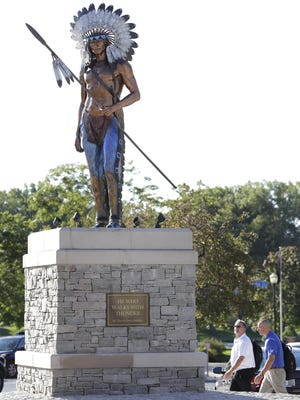 """Daniel Kortan (left) checks out the statue """"He Who Walks with Thunder"""" as he walks with Ron Raush in September in downtown Menasha. The statue was created by sculptor David L. Spellerberg and was installed on Main Street. The Native American figure in bronze was inspired by the respected Winnebago Chief Hootschope, who led a tribe in this area in the early 1800s. Businessman John Bergstrom commissioned and paid for the original sculpture as a gift to the community. It's on a parcel of land owned by Bergstrom Properties."""