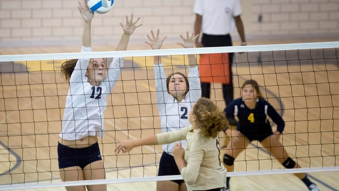 Port Huron Northern junior Halle Shell jumps to block the ball along with senior Kira Scahill during a volleyball game Tuesday, September 27, 2016 at Port Huron Northern High School.