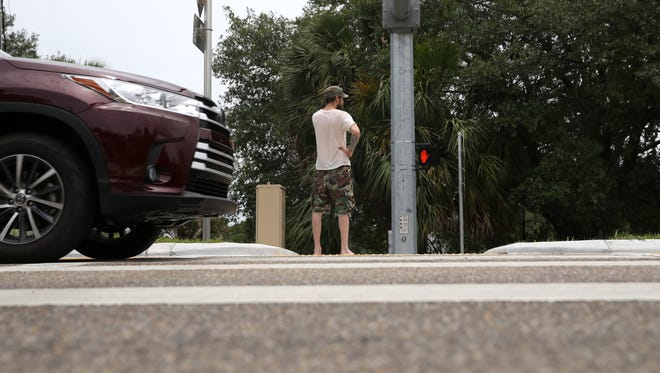 A man crosses the street near Lake Ella where a newly installed crosswalk on Monroe Street was built to increase safe pedestrian use along the busy thoroughfare.
