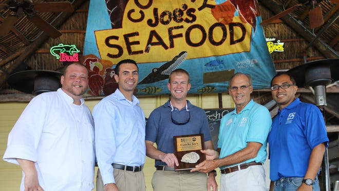 Conchy Joe's president and owner Fritz Ayres acceps the Oyster Award from Florida Oceanographic Society's Executive Director Mark Perry. From left, Brad Latif, Nicholas Darley, Fritz Ayres, Mark Perry, and Vincent Encomio.