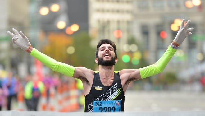 Zachary Ornelas, 24, of Ann Arbor crosses the finish line in first place Sunday in the Detroit International Marathon.