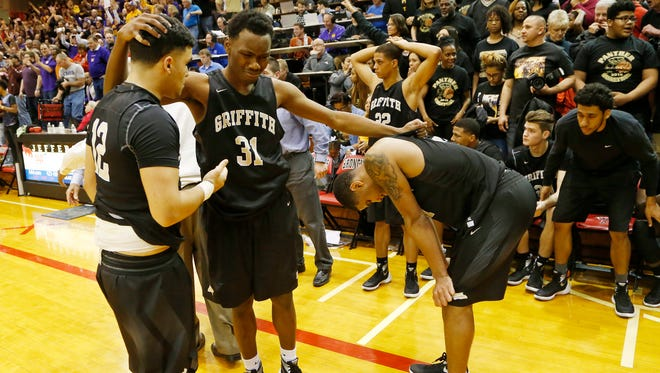 Griffith players Anthony Quintero (12), from left, Torin Dillon (31) and Anthony Murphy (21) console one another after losing to Marion 60-58 in the  Class 3A basketball semistate Wednesday, March 23, 2016, Lafayette Jefferson High School.