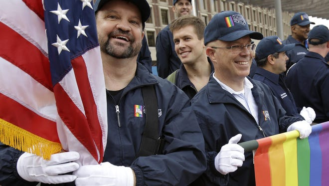 Retired U.S. Air Force Master Sgt. Eric Bullen, left, holds an American flag as U.S. Army veteran Ian Ryan rolls up an OutVets banner after marching in a Veterans Day parade in Boston on Nov.11.