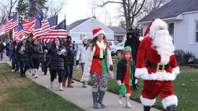 "Friends and the ""Rolling Thunder"" group march down Birchlawn street lead by Santa to the Ralston family home."