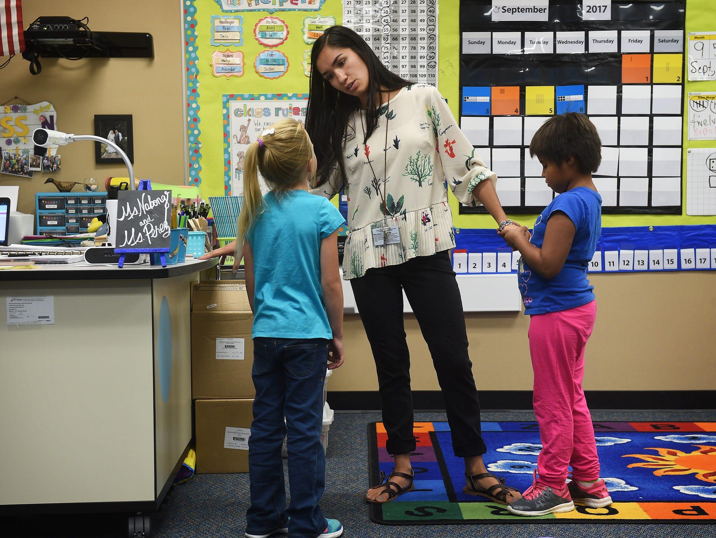 First grade teacher Marisa Nabong talks to a student