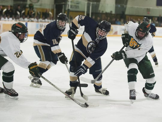 Essex's Henry Adams (15) battles for the puck with BFA's Connor Wood (22) and Collin Manahan (12) during the boys hockey game between the Essex Hornets and the BFA St. Albans Bobwhites earlier this season.