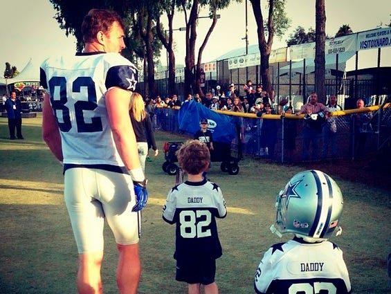 """Cowboys' Jason Witten walks with his children, who are wearing jerseys that say """"Daddy"""" on the back."""