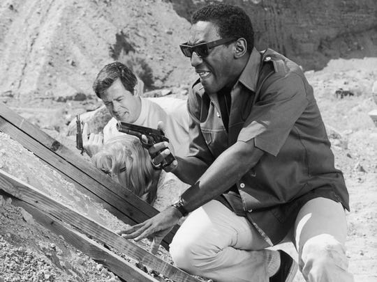 "Robert Culp, left, and Bill Cosby hold guns and crouch behind a mound of dirt in a still from the TV series ""I Spy"" in the mid-1960s."