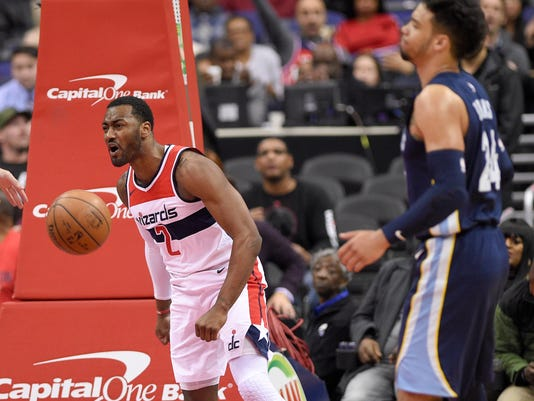 Washington Wizards guard John Wall (2) reacts after his dunk during the first half of an NBA basketball game next to Memphis Grizzlies forward Dillon Brooks (24), Wednesday, Dec. 13, 2017, in Washington. (AP Photo/Nick Wass)