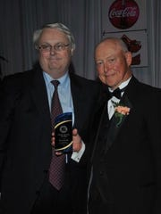 Gary Smith, right, receives the Eddie Meath Award from Kevin Meath