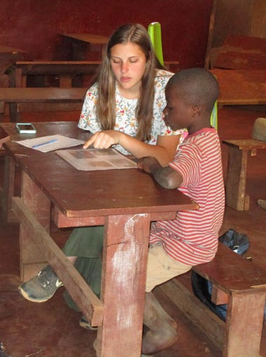Danielle Snyder, 17, works with a student at a school in Njewa, Malawi. Snyder traveled there for humanitarian service this summer with her former second-grade teacher Kim Witte.