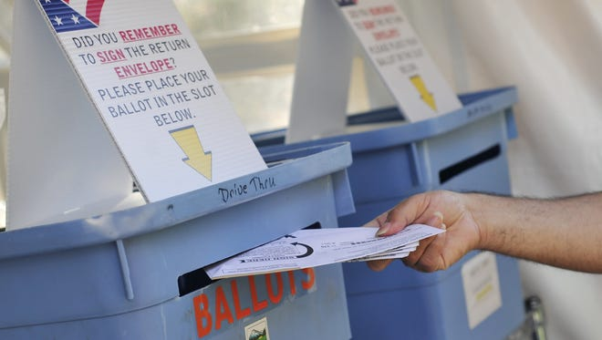 Voters drop off ballots at a drop site outside the Marion County Courthouse in downtown Salem in this file photo.