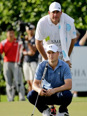 Jordan Spieth discusses his shot with caddie Jay Danzi on the 13th hole during the first round of the SMBC Singapore Open. Danzi is a Vestal graduate.