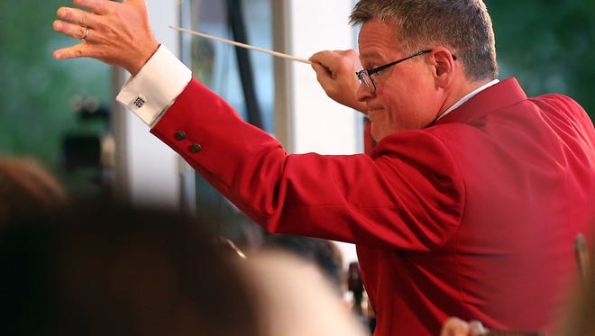 John Morris Russell, conductor of the Cincinnati Pops Orchestra, throws out the first pitch at the Reds-ArtsWave game Aug. 7. Holding the baton in his right hand, we're guessing he's a righty.