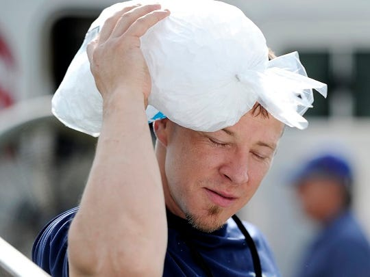 Isaac Gunn places a bag of ice on his head while working