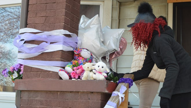 Natasha Baker, 21, of Milwaukee, decorates a home in the 2300 block of N. 41st St. where Stephanie Jones, 18, was shot and killed on Tuesday. Jones' family gathered for a vigil Saturday in her honor.