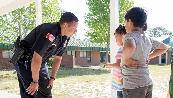 Off-duty Pensacola Police Department and school resource officer Michael Garcia chats with students while walking around Scenic Heights Elementary School in Pensacola on Wednesday, April 18, 2018.