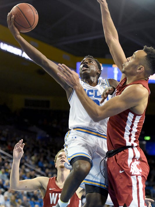 UCLA's Aaron Holiday (3) shoots against Washington State's Arinze Chidom during the first half of an NCAA college basketball game Friday, Dec. 29, 2017, in Los Angeles. (AP Photo/Michael Owen Baker)