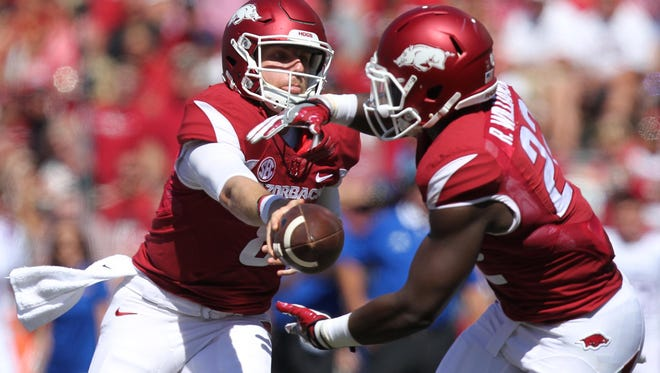 Arkansas quarter back Austin Allen, left, hands the ball off to running back Rawleigh Williams III during the first half on Saturday in Fayetteville, Ark.