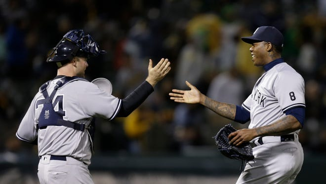 New York Yankees pitcher Aroldis Chapman, right, celebrates with Brian McCann at the end of a baseball game against the Oakland Athletics on Thursday, May 19, 2016, in Oakland, Calif. The Yankees won 4-1.