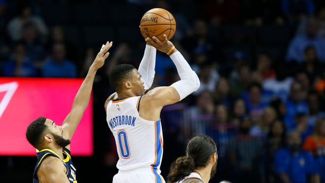Oklahoma City Thunder guard Russell Westbrook (0) shoots between Indiana Pacers guard Cory Joseph, left, and guard Darren Collison, right, in the second quarter of an NBA basketball game in Oklahoma City, Wednesday, Oct. 25, 2017.
