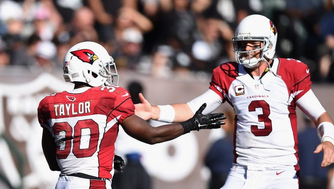Carson Palmer #3 of the Arizona Cardinals celebrates a touchdown with teammate Stepfan Taylor #30 of the Arizona Cardinals in the second quarter against the Oakland Raiders at O.co Coliseum on October 19, 2014 in Oakland, California.