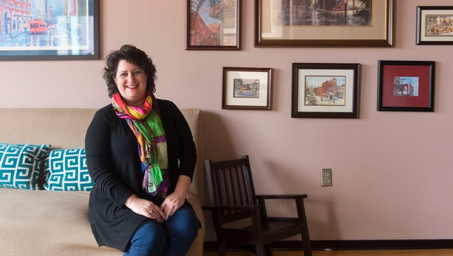 Kim Henry sits in her living room in front of some of her collection of local art. The rocking chair belonged to her father.