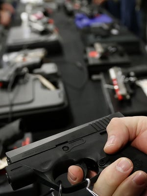 A man holds a Beretta U.S.A. Corp. handgun for sale at the Rocky Mountain Gun Show in Sandy, Utah. Gun-related issues have been on the rise in Lafayette from previous years.