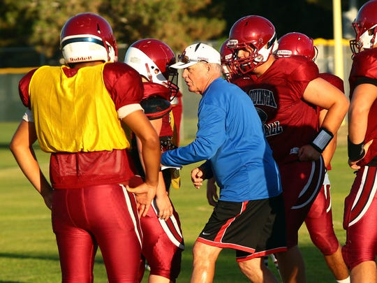 La Quinta High School football coach Dan Armstrong works with his team during early morning practice on Thursday, August 14, 2014 in La Quinta, Calif.