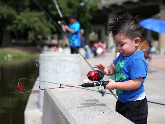 Abel Martinez, 2, fishes from Celebration Bridge during the Standard-Times Outdoor Family Fun Day on Saturday (Adam Sauceda/Standard-Times).