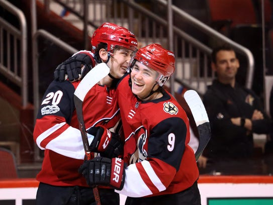 Coyotes center Dylan Strome (20) celebrates his first career goal with Clayton Keller on Saturday.