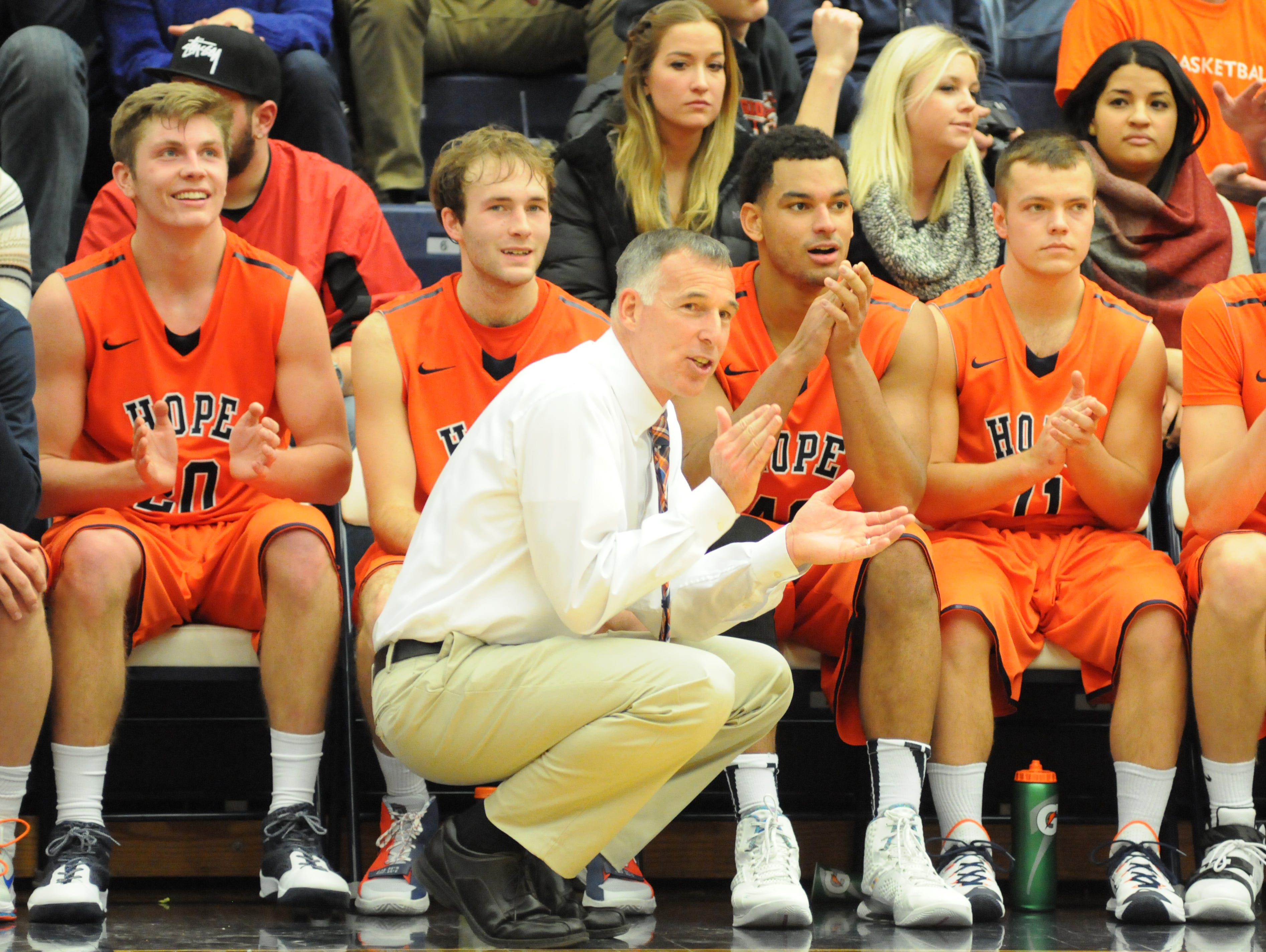 Okemos native and Hope College basketball coach Greg Mitchell claps as he watches his team taking on Trine last season.