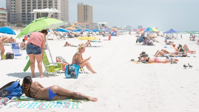 Sun worshipers enjoy a beautiful day at Pensacola Beach on Wednesday, May 17, 2017.