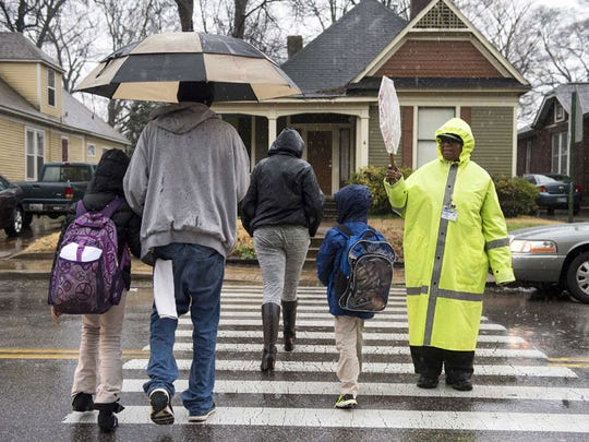 Crossing guard Hattie Williams (right) helps Memphis students and their parents cross the street in the rain after school in 2016.