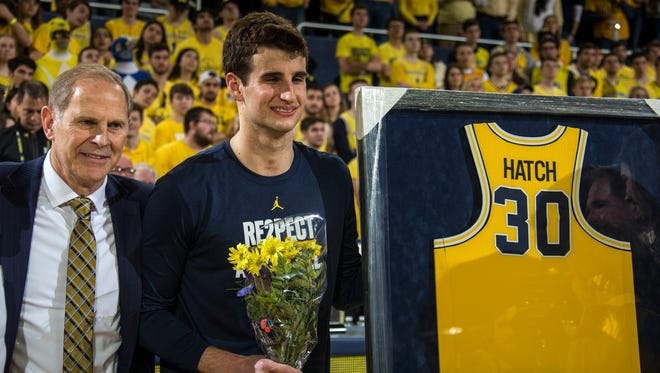 Michigan coach John Beilein, left, stands with Austin Hatch, center, to honor Hatch's participation with the Michigan basketball team during senior day celebrations prior to the game against Ohio State at Crisler Center in Ann Arbor on Sunday, Feb. 18, 2018. Hatch is a two-time plane crash survivor, played for Michigan as a freshman, and has been a student assistant since 2015.