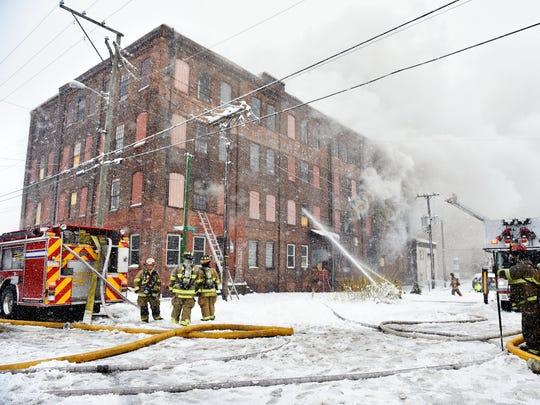 Firefighters work the scene in snow on March 21, 2018,