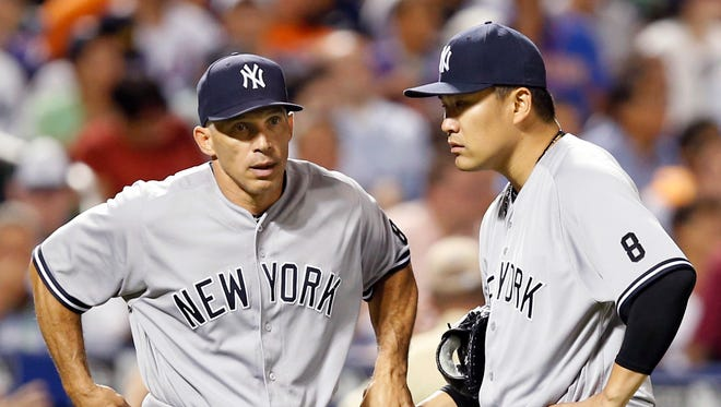 New York Yankees manager Joe Girardi grabs the ball from New York Yankees starting pitcher Masahiro Tanaka (19) dduring the seventh inning of an interleague baseball game after Tanaka allowed seven runs on eight hits in six and a third innings, Tuesday, Aug. 2, 2016, in New York.
