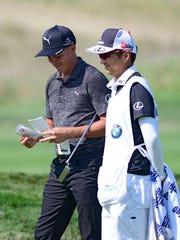 Rickie Fowler looks at his book during the second round of the BMW Championship golf tournament at Conway Farms Golf Club.  The USGA and R&A stated in May that the ruling bodies are looking at the legality of green-reading books.