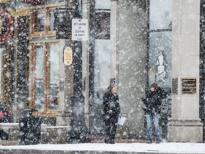 Heavy snowfall limits visibility in the downtown area