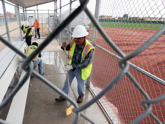 Workers use a power washer to clean a dugout at the