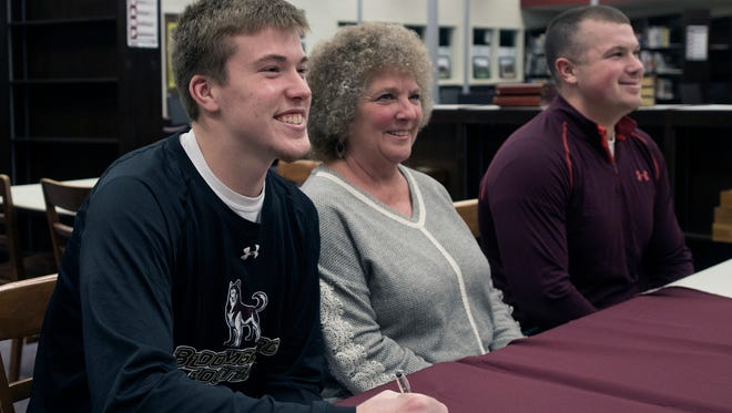 Carter Van Scyoc, left,  signs a letter of intent on Wednesday, March 28, 2018, to play football for Bloomsburg University. Also pictured was Cathy Van Scyoc, Carter's mother, and his brother Spencer.